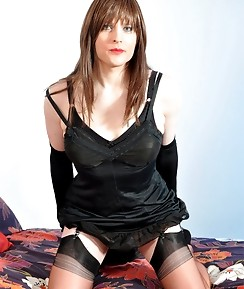 Sexy TGirl posing on a big bed wearing a black dress