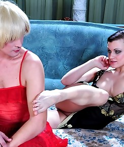 Sissy guy in a red nighty and fishnets shares a dildo with a dominative gal